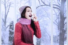 Woman in winter clothes sneezing Royalty Free Stock Image