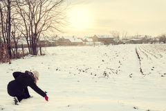 Woman in winter clothes in snow drawing with finger love Stock Photography