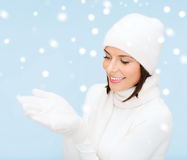 Woman in winter clothes with something on palms Stock Photo