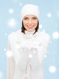 Woman in winter clothes with something on palms Stock Photos
