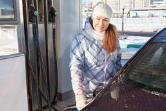 Woman in winter clothes standing with refuel pistol near car Stock Image