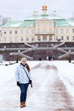 Woman in winter clothes stands in front of the main staircase Menshikov Palace in Oranienbaum Royalty Free Stock Photography