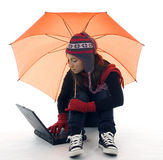Woman in winter clothes with umbrella and laptop Stock Image