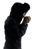Woman winter coat drinking hot drink  silhouette Royalty Free Stock Photography