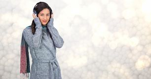 Woman in winter coat listening to music on headphones. Digital composite of Woman in winter coat listening to music on headphones Stock Images