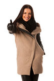 Woman in winter coat standing confidently, showing thumb up  and Stock Photo