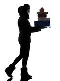 Woman winter coat walking carrying christmas gifts silhouette Royalty Free Stock Photo