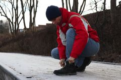 Woman on a winter day tying her shoes, prepare for walking royalty free stock photo