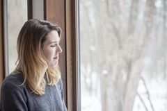 Woman with winter depression. A sad young woman wearing a sweater by window at home inside winter royalty free stock photos