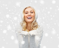 Woman in winter earmuffs showing empty palms Stock Images