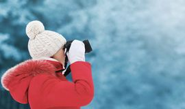 Woman in winter, female photographer takes picture on digital camera. Outdoors in cold day on blurred forest background, empty copy space, view profile royalty free stock images
