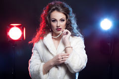 Woman in winter fur with jewellery and two lights behind Royalty Free Stock Images