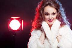 Woman in winter fur with red light behind on black background Stock Photos
