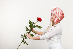 Woman in winter furry hat holding red rose Stock Photo