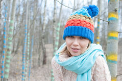 Woman winter hat. Woman in winter in forest colored tree sream Royalty Free Stock Photography