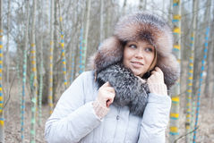 Woman winter hat. Woman in fur russian hat in forest colored tree sream Stock Photos