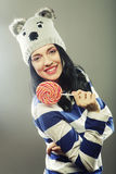 Woman with winter hat holding big lollipop Royalty Free Stock Image