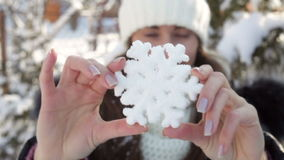 Woman in winter hat holding big snowflake stock footage