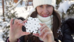 Woman in winter hat holding big snowflake stock video footage