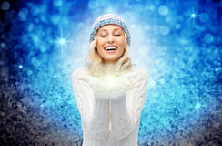 Woman in winter hat holding fairy dust on palms Stock Image