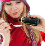 Woman in winter hat with spoon of syrup Stock Photo