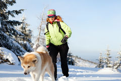Woman winter hiking with dog Royalty Free Stock Photos