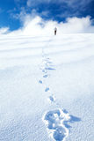 Woman on winter holidays. Woman spending wintertime holidays in the mountains covered with beautiful white snow, standing on the top of mountain and enjoying Stock Photo