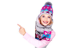 Woman in winter outerwear  holds the banner and points on it Royalty Free Stock Image