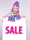 Woman in winter outerwear  holds the white banner with sale word Royalty Free Stock Photo