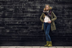 Woman in Winter Outfit in Front Old Gray Wall Stock Image