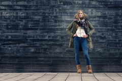 Woman in Winter Outfit in Front Old Gray Wall Royalty Free Stock Photography