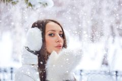 Woman in winter park blowing on snow Stock Photography