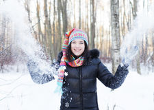Woman in winter park, blowing snow playfully Stock Photo