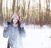 Woman in winter park, blowing snow playfully Stock Image
