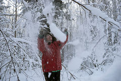 Woman in winter Park clears snow from a branch laughing Stock Images