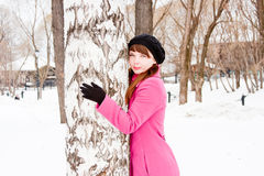 Woman in a winter park near a birch Royalty Free Stock Image