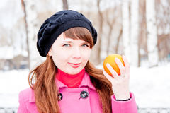 Woman in winter in a park with orange in hands Royalty Free Stock Images