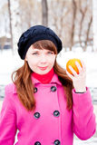 Woman in winter in a park with orange in hands Stock Photo