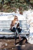 Woman in a winter park sits on a bench Stock Images
