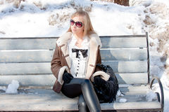 Woman in a winter park sits on a bench Royalty Free Stock Photos