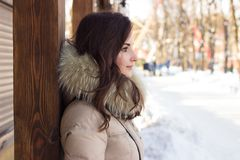 Woman in winter park. Near some buildings Stock Image