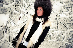 Woman winter portrait. A young woman standing near snow covered tree branches in a stylish winter coat and hat Stock Images