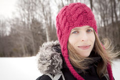 Woman winter portrait. Picture of a woman with beautiful blue eyes, in her thirties, looking and smiling at the camera. She is outdoors, in front of a forest Stock Photography