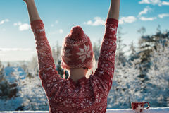 Woman in winter. Portrait of woman wearing red and white sweater standing with extended arms in outdoor snowy winter landscape Stock Image