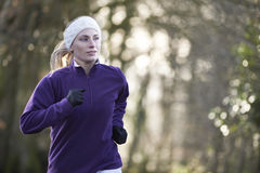 Woman On Winter Run Through Woodland. Young Woman On Winter Run Through Woodland stock photo