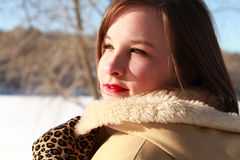 Woman winter's beauty. Closeup of a smiling beautiful woman outdoors in winter with fur trimmed coat and leopard gloves in the snow Royalty Free Stock Image