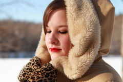 Woman winter's beauty with eyes downcast. Closeup of a slightly smiling beautiful woman outdoors in winter with fur trimmed coat and leopard gloves in the snow Stock Photos