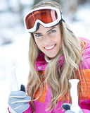 Woman in winter on a ski trip holding poles Royalty Free Stock Photo