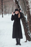 Woman winter snow nature portrait in black coat and hat.  Royalty Free Stock Image