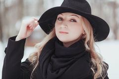 Woman winter snow nature portrait in black coat and hat.  Stock Photography